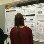 Picture of UVA Poster judge Tajie Harris listening to poster presentation at UVA symposium.