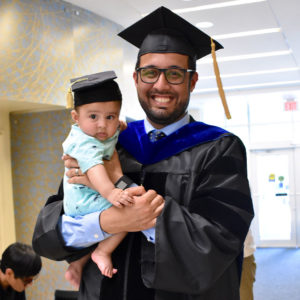 Student in cap in gown with baby in small graduation cap