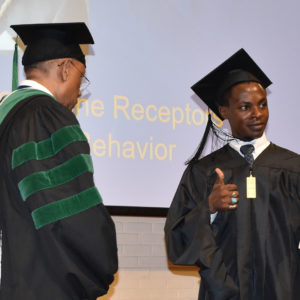 Student giving a thumbs up as he receives his diploma