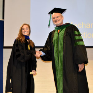 Student smiling as she receives diploma