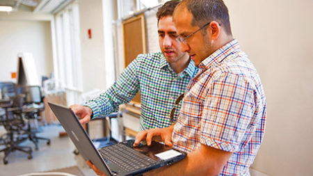 2 male scientists viewing laptop