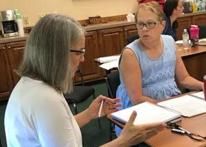 women sitting down at table talking