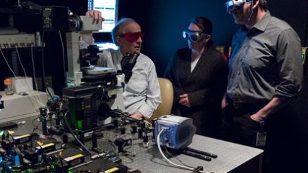 Two people looking through a laser microscope.