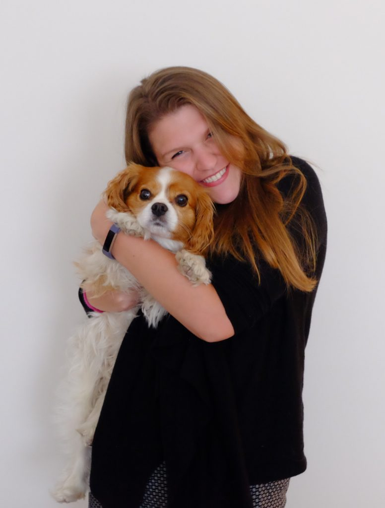 portrait of Andrea Zeke hugging a dog