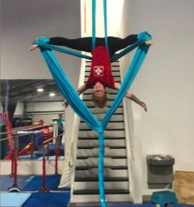 portrait of Kellie Mitchell performing aerial yoga