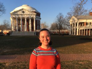 portrait of Pamela Moore standing on UVA Lawn with Rotunda in background