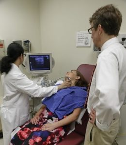 Performing a throat ultrasound.