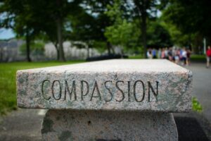 """Word """"compassion"""" written on stone bench."""