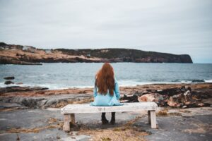 Woman sitting on a stone bench by the sea