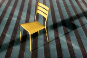 Wooden chair on striped carpet.