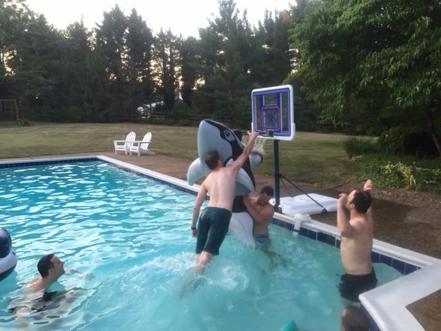 Max Hoggard dunks over Ian Dempsey and a giant inflatable orca in a pool basketball game with Jourdan Cancienne and Eric Larson