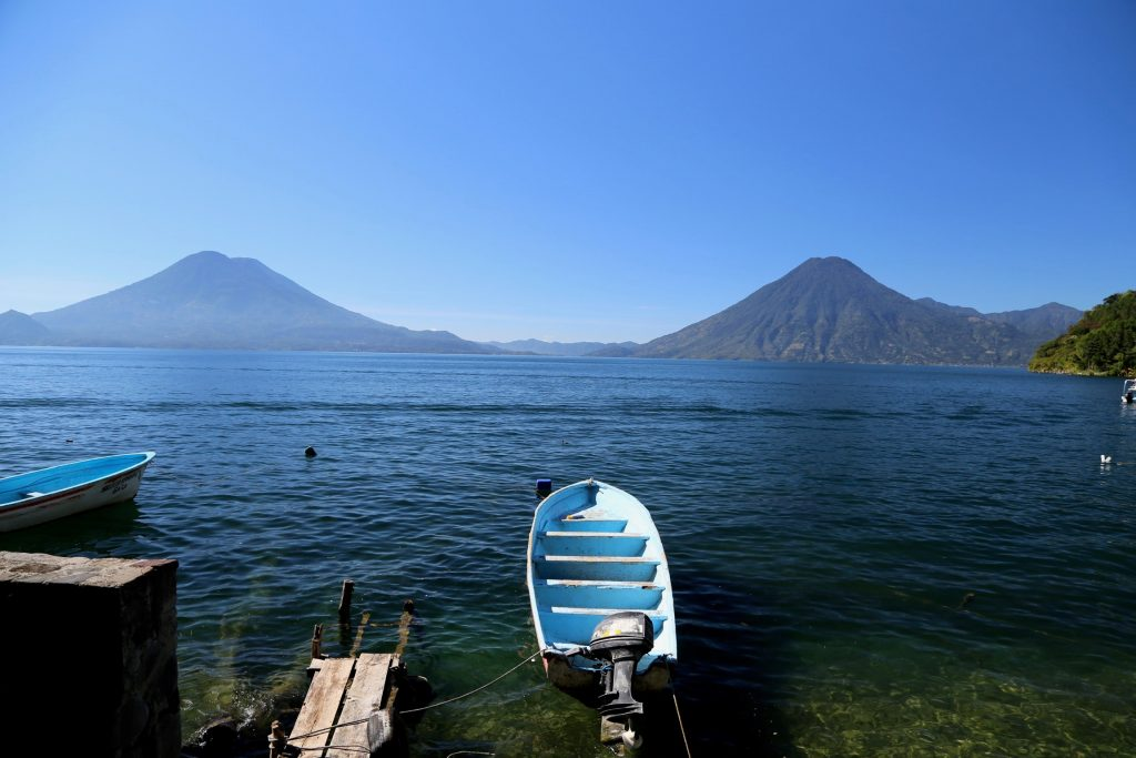 Boat in water in front of Guatemalan volcano