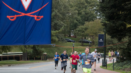 runners on road with UVA flag
