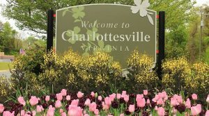 A sign for Charlottesville stands behind a bed of pink flowers