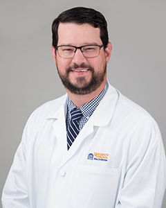 Radiologist Cody Quirk posing for headshot in glasses and white coat