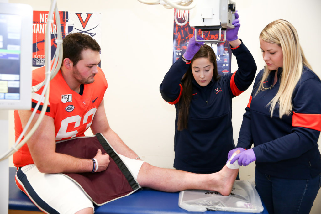 Samantha and Taylor position the player's leg to take an x-ray