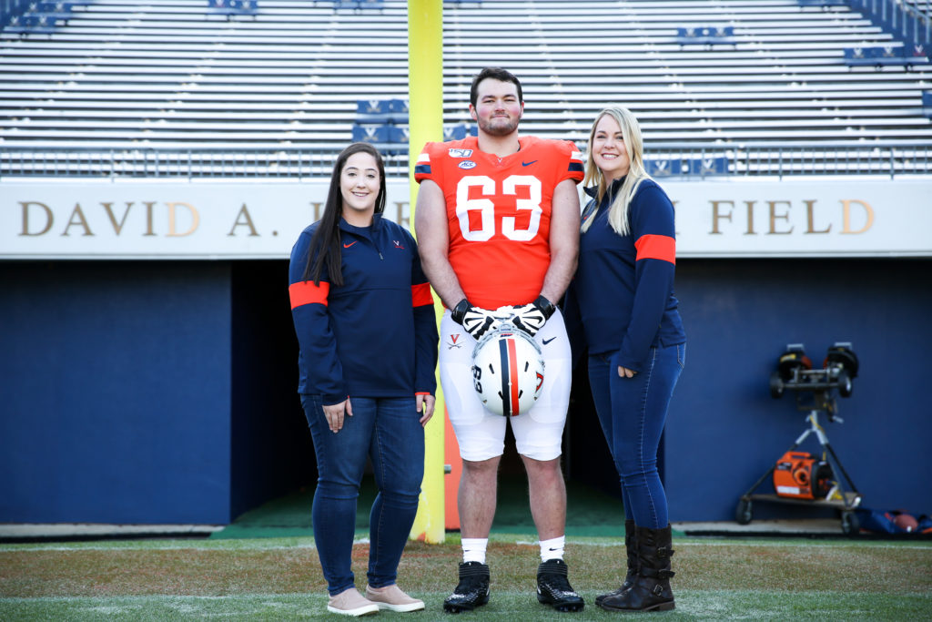 Diagnostic Radiological Technonolists Taylor Burton, left, and Smanatha Shoemaker, right, pose with a UVA football player Tyler Fannin
