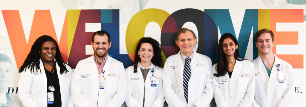 UVA Radiology's Diversity and Inclusion representatives pose with Dr. Juliana Bueno and Dr. Eduard de Lange in front of the welcome sign the main hospital lobby