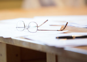 glasses on desk with papers and pen