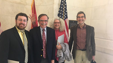 Dr. Tamm with three other people standing in front of two flags