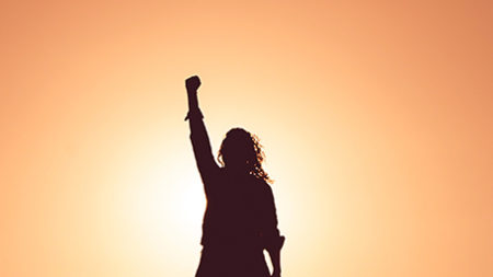 Silhouette of a woman with a triumphant fist in the air
