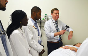 Photo of Dr.Parsons Teaching three residence with real patient