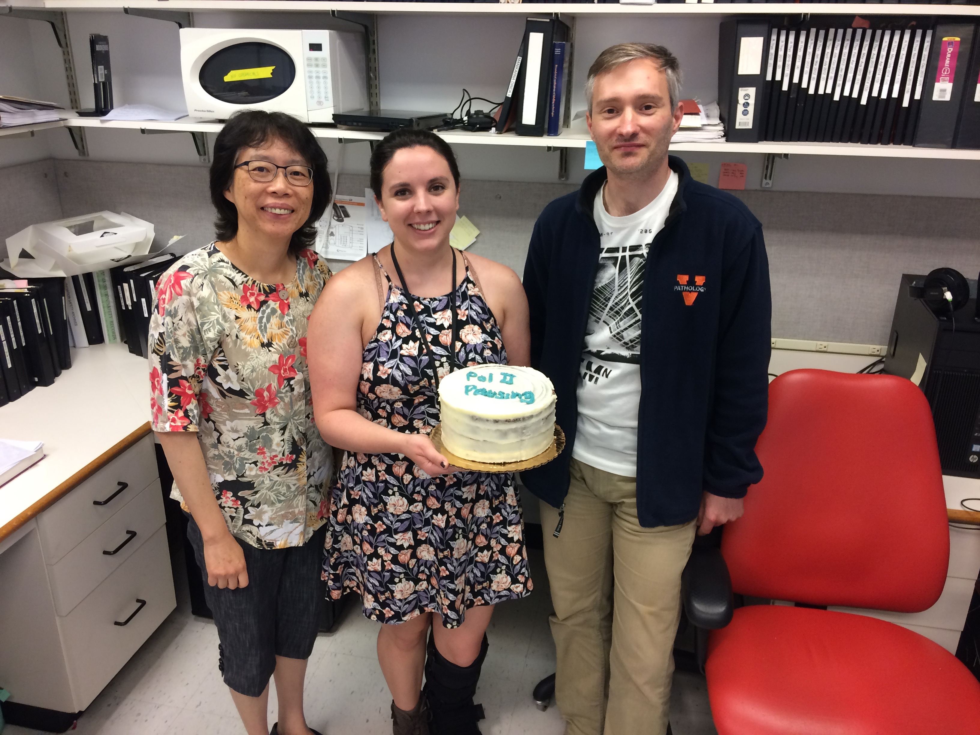 Image of Dr. Yuh-Hwa Wang, Naomi Atkin, and Karol Szlachta with a cake celebrating the pausing paper