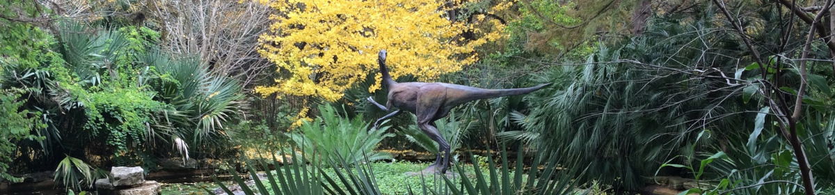 Banner image of a dinosaur sculpture in trees